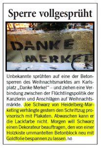 """Betonpoller besprüht mit """"Danke Merkel"""" auf dem Heidelberger Weihnachtsmarkt. Joe Schwarz von Heidelberg Marketing entfernt den Schriftzug!"""